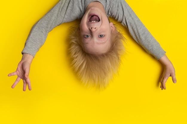 Ein verängstigter junge mit blonden langen haaren hängt kopfüber und schreit. Premium Fotos