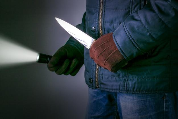 Ein verbrecher mit einer messerwaffe droht zu töten. verbrechen konzepte raub konzepte Premium Fotos