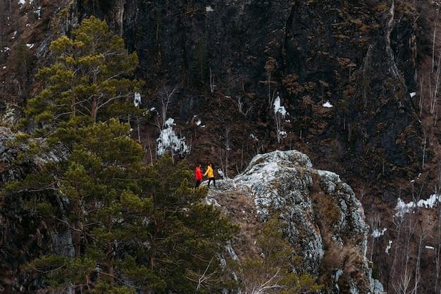 Ein verliebtes paar, das in die berge reist. mann und mädchen unterwegs. paar in den bergen ausruhen. mann und frau im sport. den berg besteigen. in den bergen wandern. Premium Fotos