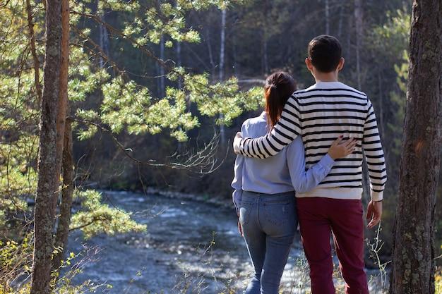 Ein verliebtes paar, ein mann und ein mädchen stehen in der natur in der nähe des flusses und freuen sich. Premium Fotos