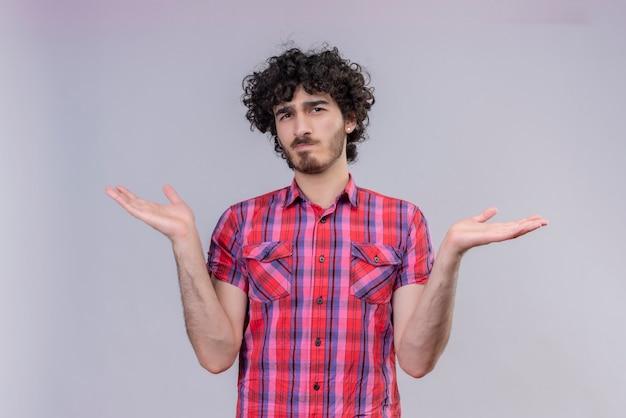 Ein verwirrter gutaussehender mann mit lockigem haar in kariertem hemd und offenen armen Kostenlose Fotos