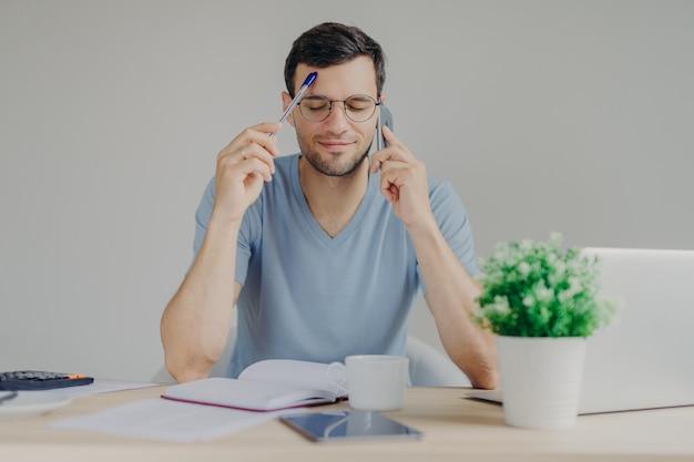 Ein vielbeschäftigter mann arbeitet an organisatorischen fragen, spricht mit dem geschäftspartner über das handy, hält die augen geschlossen und versucht, sich die notwendigen informationen zu merken Premium Fotos