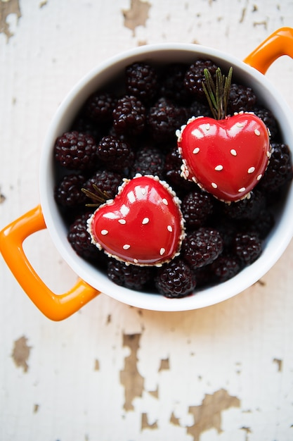 Ein voller brombeerteller mit herzförmigem dessert Premium Fotos