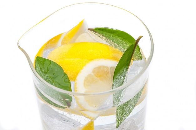 Ein voller krug getränk aus eis, läppchen frisch saftiger gelber zitrone und kristallklares wasser. Premium Fotos