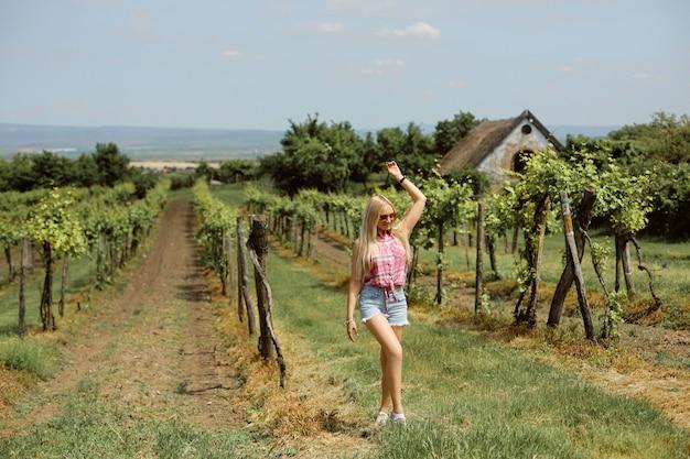 Ein vorbildliches mädchen in einem rosa hemd und jeansshorts geht durch den weinberg auf dem land. sommerreisekonzept Premium Fotos