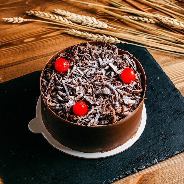 Ein vorderansicht-schokokuchen verziert mit schokoladencreme-roten kirschen innerhalb des braunen kuchenpfannenfeiertags köstlichen geburtstages auf dem braunen hintergrund Kostenlose Fotos