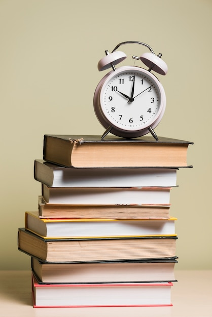 Ein wecker oben auf staplungsbüchern über hölzernem schreibtisch Kostenlose Fotos