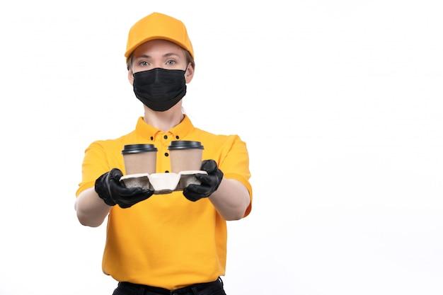 Ein weiblicher kurier der vorderansicht in den schwarzen handschuhen der gelben uniform und der schwarzen maske, die kaffeetassen hält, die bestellung liefern Kostenlose Fotos