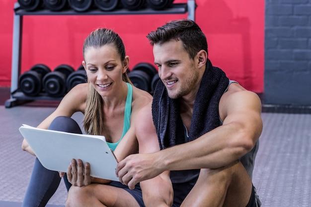 Ein weiblicher trainer, der richtlinien mit klemmbrett erklärt Premium Fotos