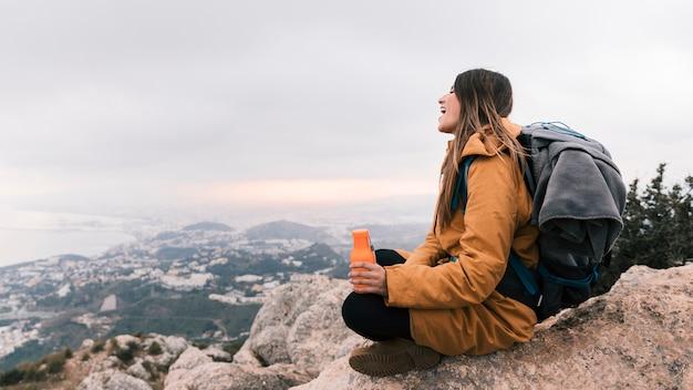 Ein weiblicher wanderer, der in der hand auf die oberseite des berges hält wasserflasche die ansicht übersehend sitzt Kostenlose Fotos