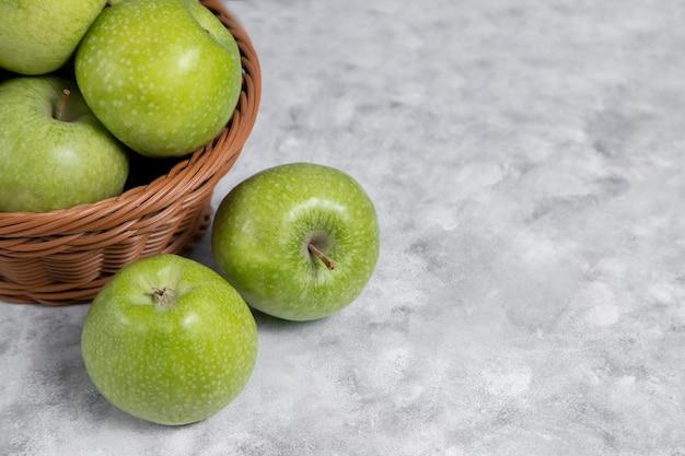 Ein weidenkorb mit frischen grünen äpfeln auf stein Kostenlose Fotos