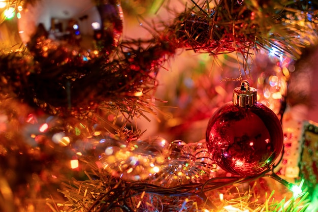 Ein weihnachtsbaumspielzeug in form einer roten weihnachtskugel hängt an einem fichtenzweig, umgeben von neujahrsdekorationen Premium Fotos