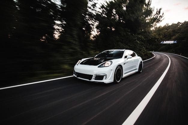 Ein weißer sportwagen mit schwarzem autotuning, der mit hoher geschwindigkeit auf der straße fährt. Kostenlose Fotos
