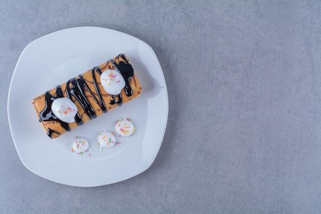 Ein weißer teller mit süßem, köstlichem brötchen mit schokoladensirup. Kostenlose Fotos