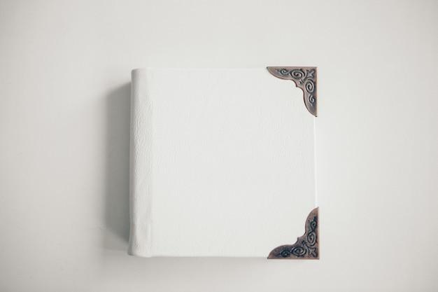 Ein weißes buch, eingewickelt in leder auf einem weißen hintergrund. fotoalbum mit metallrahmen. grußkarte Premium Fotos