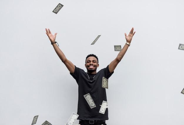 Ein wohlhabender afrikanischer mann, der sein geld wegwirft Kostenlose Fotos