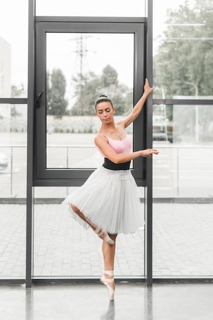 Ein würdevoller weiblicher tänzer des klassischen balletts auf pointe schuhen Kostenlose Fotos