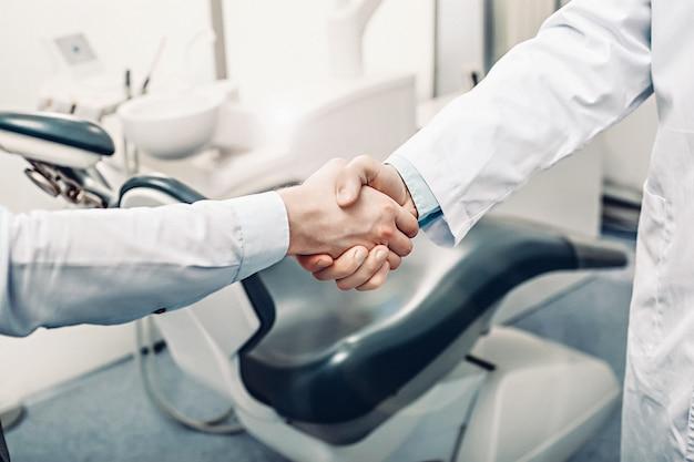 Ein zahnarzt und ein patient geben sich die hand Premium Fotos