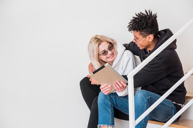 Ein zwischen verschiedenen rassen junges paar, das auf treppenhaus unter verwendung der digitalen tablette gegen weiße wand sitzt Kostenlose Fotos