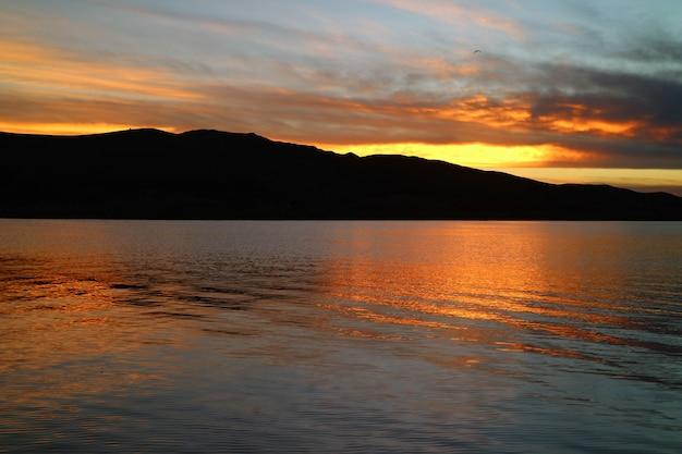 Eindrucksvolles sonnenuntergang-nachglühen, das über den berühmten titicaca-see in puno, peru nachdenkt Premium Fotos