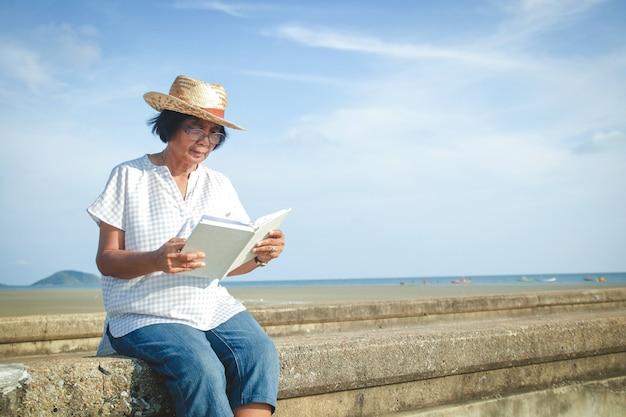 Eine ältere asiatische frau, die ein buch an der betonbrücke durch das meer liest, um frische luft sich zu entspannen und zu atmen. Premium Fotos