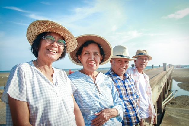 Eine ältere asiatische gruppe steht lächelnd an der betonbrücke am meer, glücklich nach dem ruhestand. Premium Fotos