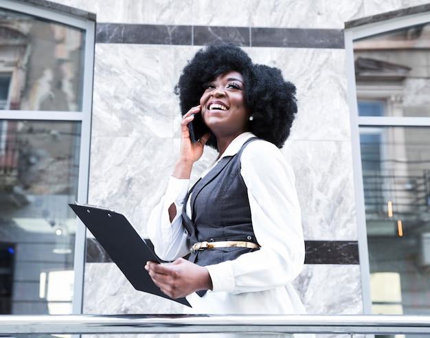 Eine afrikanische junge geschäftsfrau, die auf dem smartphone in der hand hält klemmbrett spricht Kostenlose Fotos