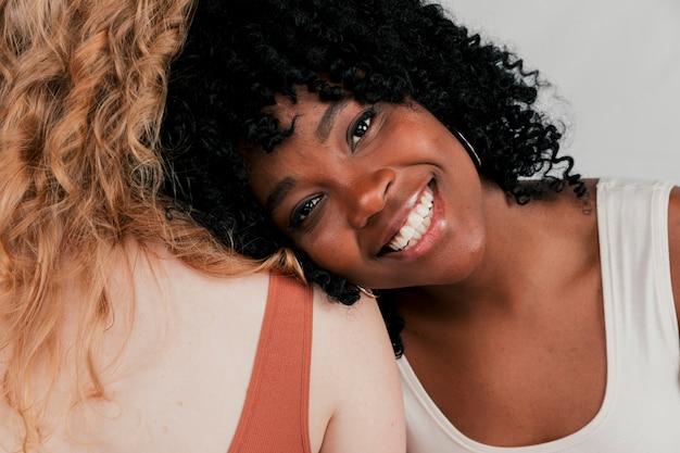 Eine afrikanische lächelnde junge frau, die auf der schulter ihres freundes mit weißer haut sich lehnt Kostenlose Fotos