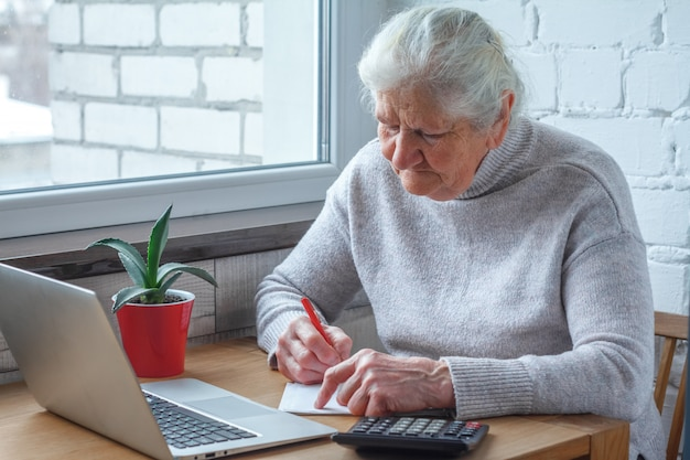 Eine alte frau sitzt am tisch vor dem laptop. Premium Fotos