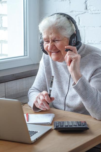Eine alte frau sitzt an einem tisch vor einem laptop mit kopfhörern und schreibt in ein notizbuch. Premium Fotos