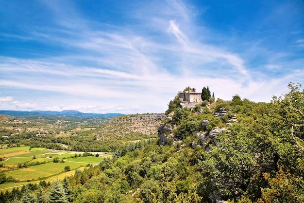 Eine alte steinkapelle, eine kirche oder ein kloster am rande eines felsens. schöne aussicht vom berg auf das tal des flusses mit feldern, wiesen, straßen, weißen, flauschigen wolken und blauem himmel. Premium Fotos