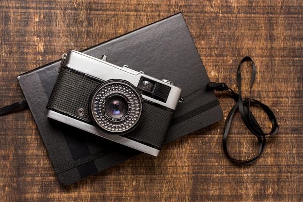 Eine altmodische kamera über dem geschlossenen tagebuch auf hölzernem schreibtisch Kostenlose Fotos