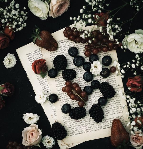 Eine ansicht von oben zeigt frische früchte wie blaubeeren und brombeeren zusammen mit anderen auf dem papier und dem dunklen boden Kostenlose Fotos