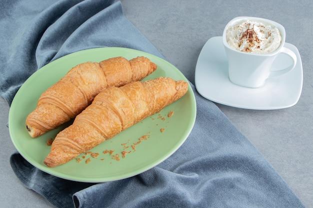 Eine anzeige des croissants im teller auf handtuch und mit kaffee, auf dem marmorhintergrund. hochwertiges foto Kostenlose Fotos