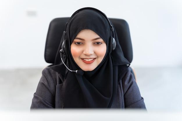 Eine arabische oder muslimische frau arbeitet in einem callcenter-betreiber und einem kundendienstmitarbeiter. sie trägt mikrofon-headsets, die am computer arbeiten, und spricht mit dem kunden, um seinen service-verstand zu unterstützen Premium Fotos