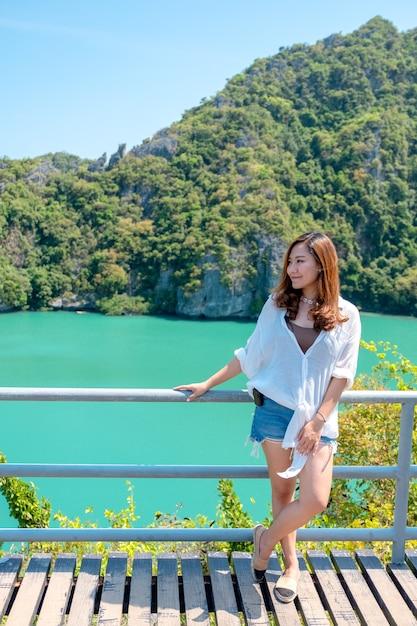 Eine asiatische frau, die am blauen meer auf der schönen landschaftsinsel steht Premium Fotos