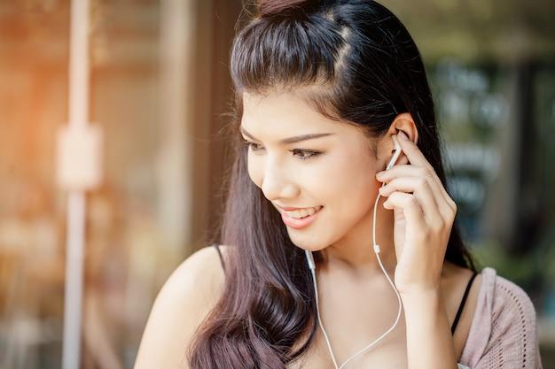 Eine asiatische frau, die musik von den kopfhörern lächelt und hört. Premium Fotos