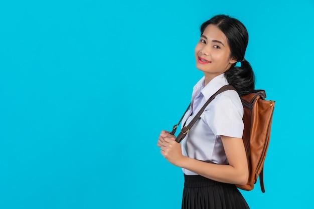 Eine asiatische studentin späht ihre braune ledertasche auf einem blauen. Kostenlose Fotos