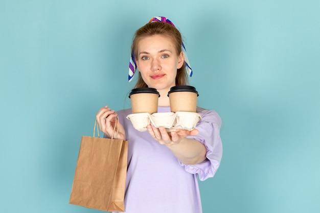 Eine attraktive frau der vorderansicht im blauen hemdkleid, das papierpaket und kaffeetassen auf blau hält Kostenlose Fotos
