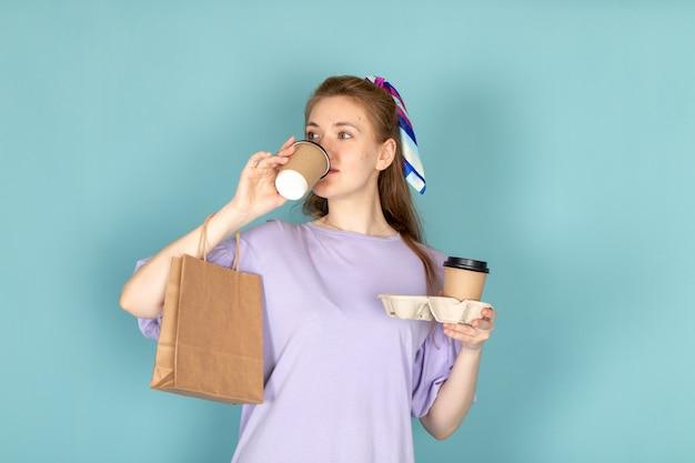 Eine attraktive frau der vorderansicht im blauen hemdkleid, das papierpaket und kaffeetassen hält, die auf blau trinken Kostenlose Fotos
