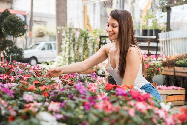 Eine attraktive glückliche junge frau, die um blühende pflanzen sich kümmert Kostenlose Fotos
