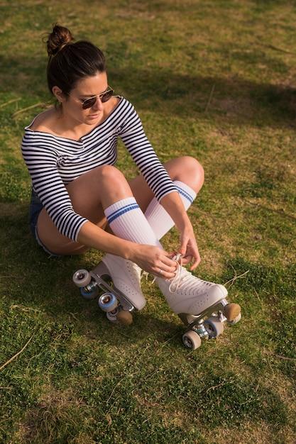 Eine attraktive junge frau, die auf dem grünen gras bindet die spitze des rollschuhs sitzt Kostenlose Fotos