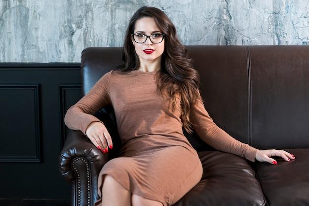 Eine attraktive junge frau, die auf dem sofa betrachtet kamera sitzt Kostenlose Fotos