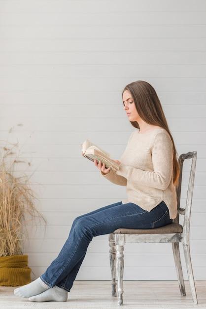 Eine attraktive junge frau, die auf holzstuhllesebuch gegen hölzerne wand sitzt Kostenlose Fotos