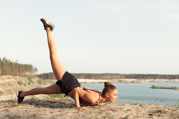 Eine attraktive junge frau, die eine yogahaltung tut Premium Fotos
