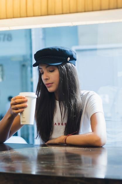 Eine attraktive junge frau, die im café in der hand betrachtet mitnehmerkaffeetasse sitzt Kostenlose Fotos