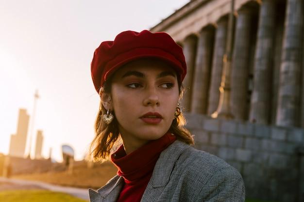 Eine attraktive junge frau in der roten kappe, die weg schaut Kostenlose Fotos