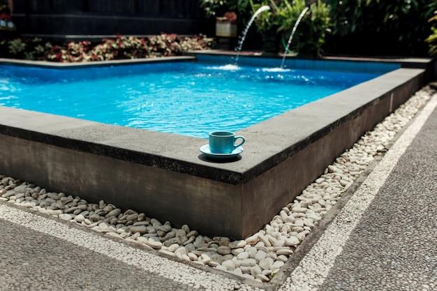 Eine blaue tasse kaffee steht an der ecke eines tropischen pools mit weißem stein bedeckt, komfortable ferien in asien Premium Fotos