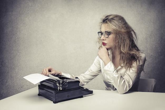 Eine blonde schriftstellerin arbeitet Premium Fotos