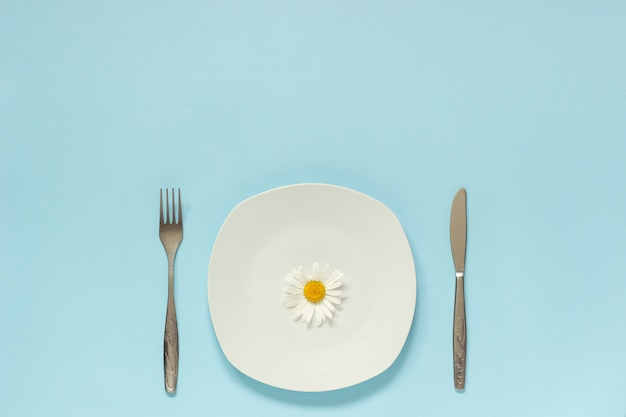Eine blumenkamille auf platte, besteckgabelmesser. konzeptvegetarier, gesunde ernährung, diät oder anorexie Premium Fotos